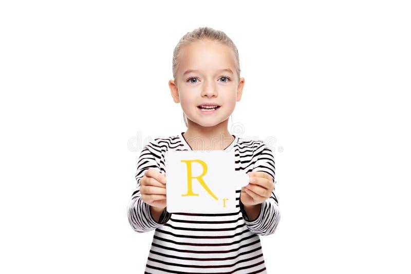 拿着与信件R的少女一张卡片 在白色背景的语言矫正概念 正确发音和清楚的发音 库存照片