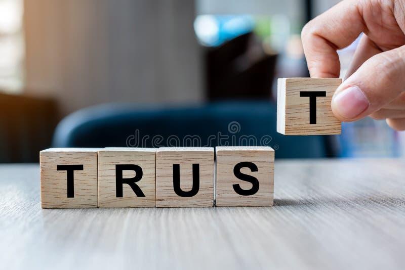 拿着与信托业务词的商人手木立方体块在桌背景 信得过,真相、信仰和协议 库存照片