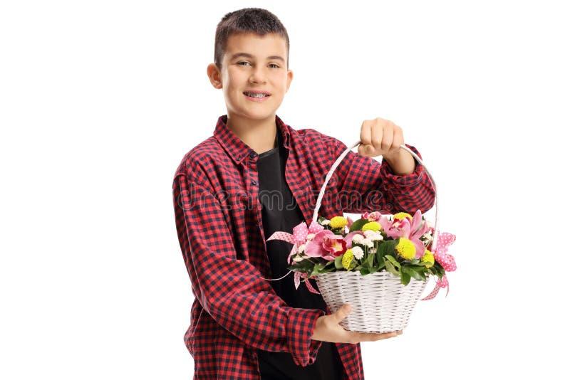 拿着与兰花和其他花的年轻男孩一个白色篮子 库存照片