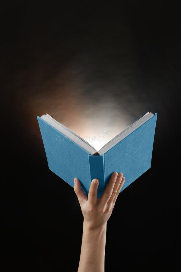 拿着与发光的女性手开放书在黑暗的背景 图库摄影