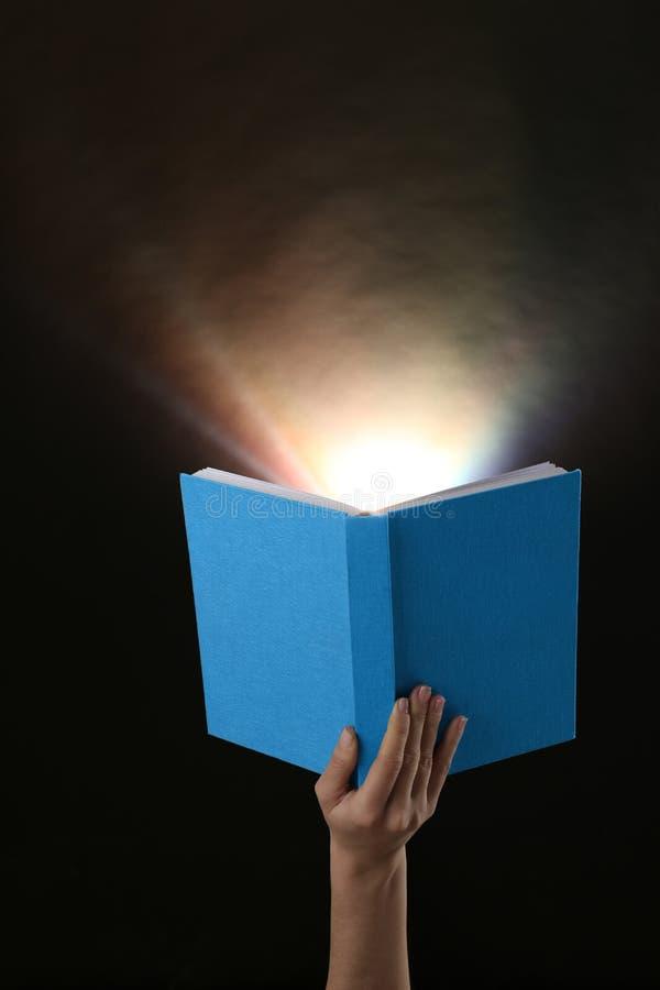 拿着与发光的女性手开放书在黑暗的背景 免版税库存照片