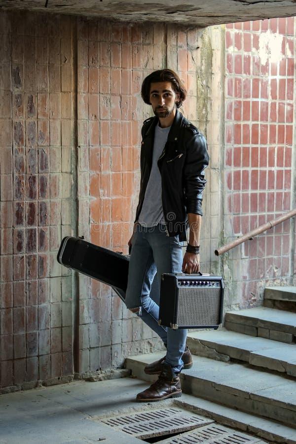 拿着与吉他和放大器的街道音乐家案件 下来了地下过道 无业游民的生活方式 挣金钱的使用a 免版税库存照片