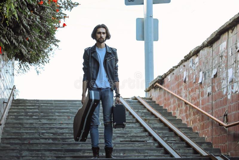 拿着与吉他和放大器的街道音乐家案件 在地下过道的步的立场 无业游民的生活方式 使用 图库摄影