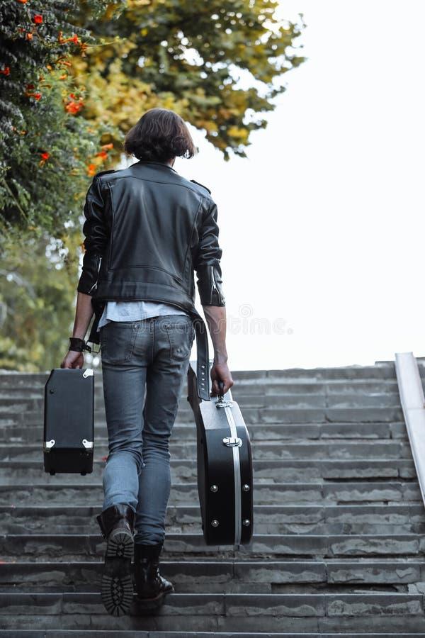 拿着与吉他和放大器的街道音乐家案件 它上升地下过道的台阶 无业游民的生活方式 使用 免版税库存照片