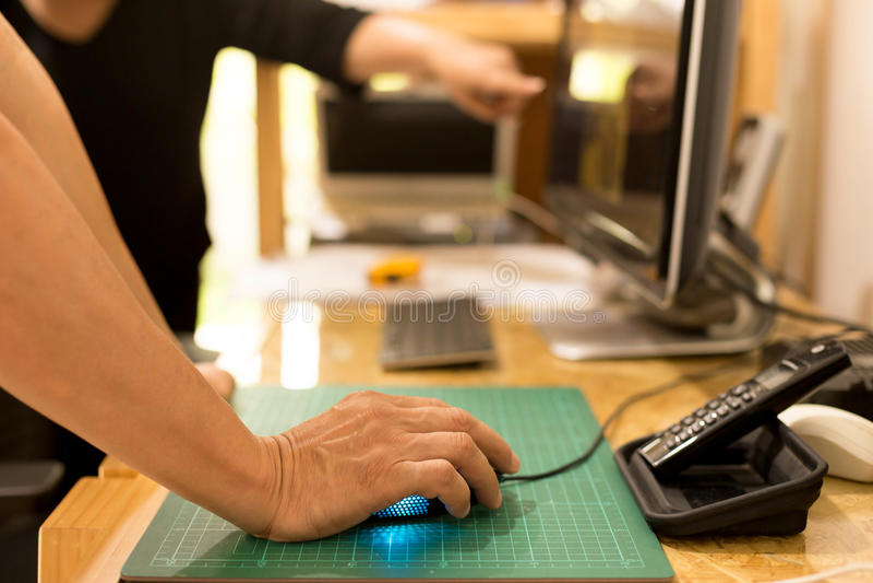 拿着与同事的商人手老鼠看comput 库存图片