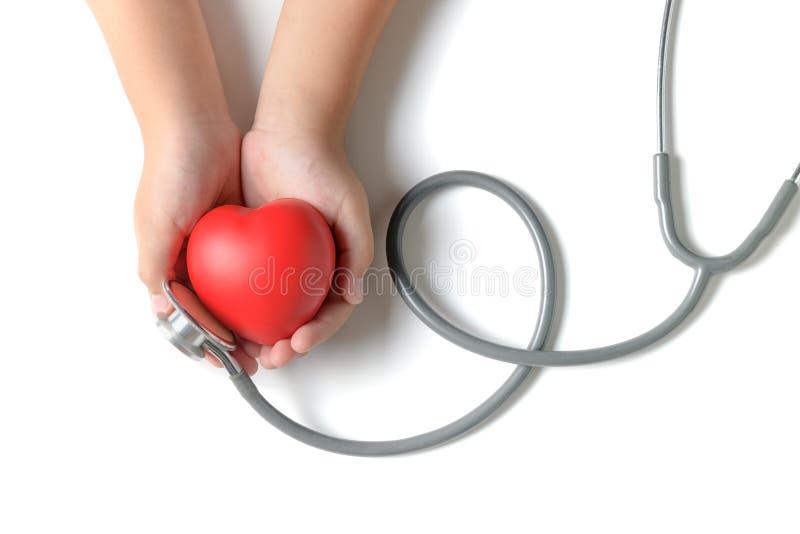 拿着与听诊器的儿童手红色心脏 免版税图库摄影