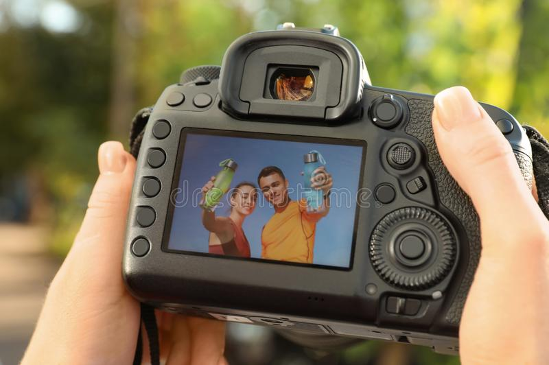 拿着与图片的女性摄影师专业照相机在屏幕上户外 免版税库存照片