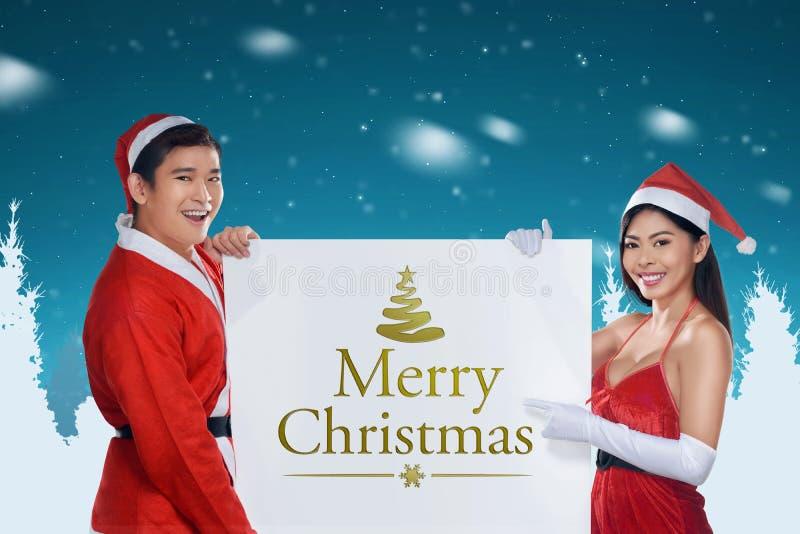 拿着与圣诞快乐消息的年轻亚洲夫妇横幅 库存照片