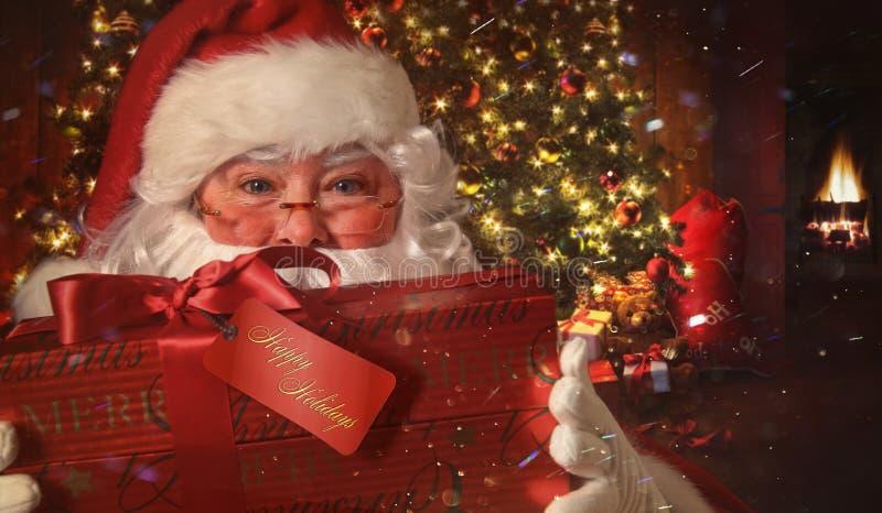 拿着与圣诞节场面的圣诞老人特写镜头礼物在背景中 免版税库存照片