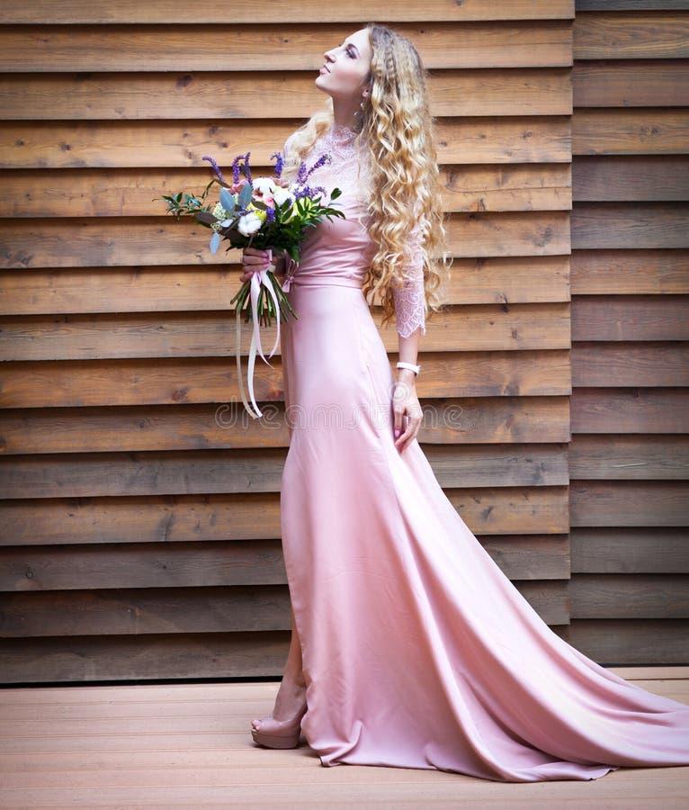 拿着与多汁花的新娘婚礼花束 免版税库存图片