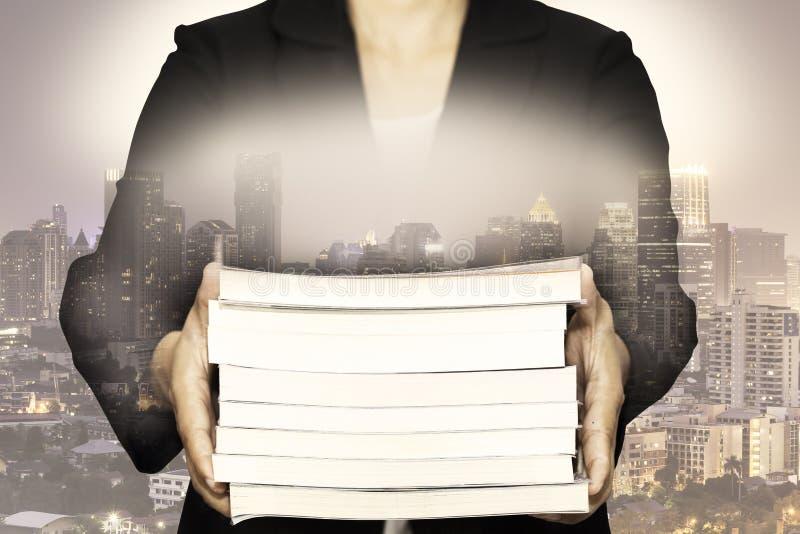 拿着与夜都市风景的事务两次曝光书 免版税库存图片