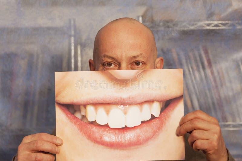 拿着与大微笑的秃头人一张卡片 免版税图库摄影
