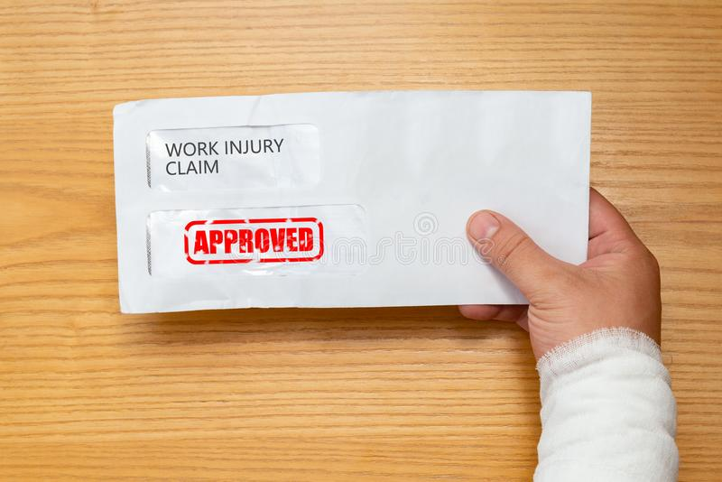 拿着与工作伤害要求应用里面的被包裹的手一个信封盖印了与批准 图库摄影