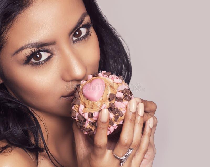 拿着与心脏的美丽的少妇杯子蛋糕 免版税库存图片
