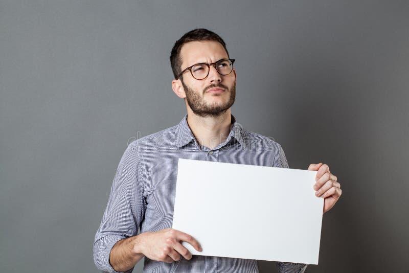 拿着与想象力的年轻商人一副空白的横幅 免版税图库摄影
