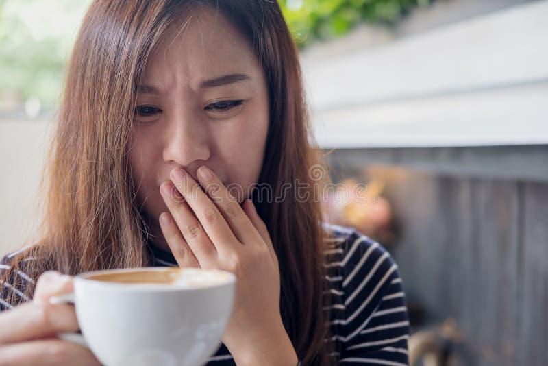 拿着与感觉的亚裔妇女热的咖啡在咖啡店的奇怪和嗅到的坏 库存图片
