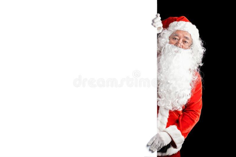 拿着与拷贝空间的愉快的圣诞老人空白的广告横幅背景 指向在白色空白的标志的微笑的圣诞老人 库存图片