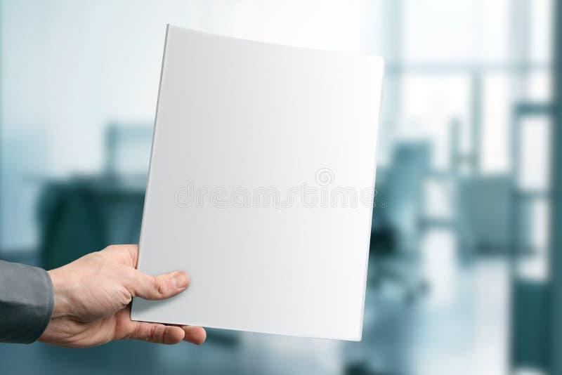 拿着与拷贝空间的手空白的杂志 免版税库存图片