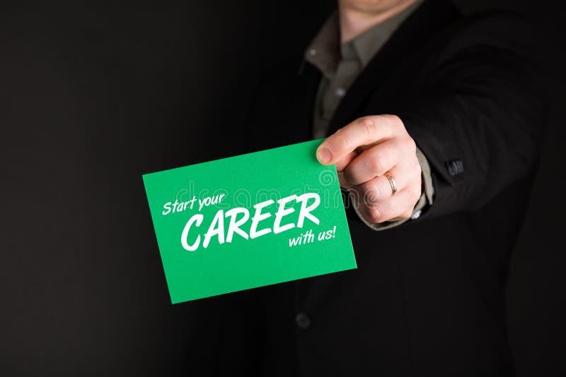 拿着与文本开始的商人绿卡您的与我们的事业! 免版税库存照片