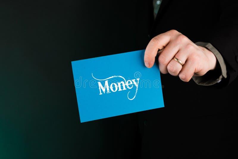 拿着与文本金钱的商人蓝色卡片 免版税库存照片