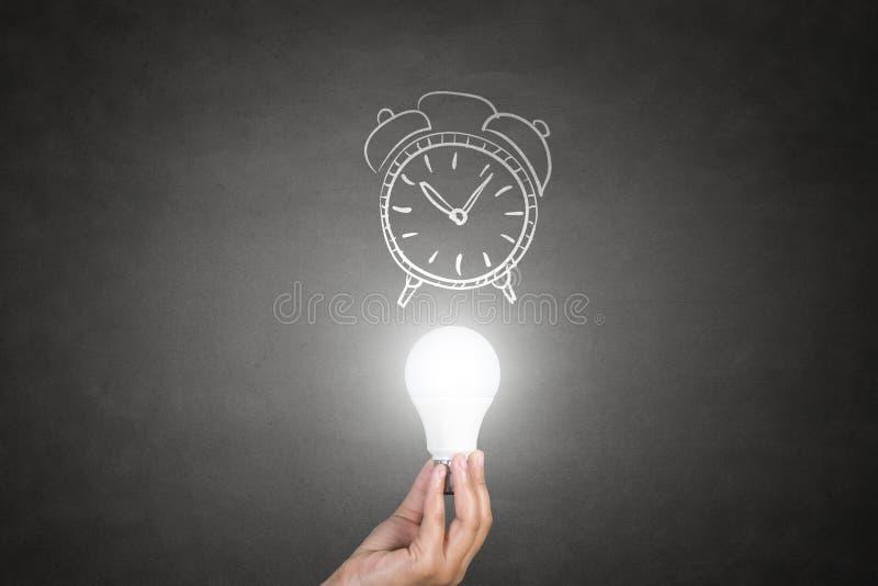 拿着与时钟的人的手电灯泡 免版税库存照片