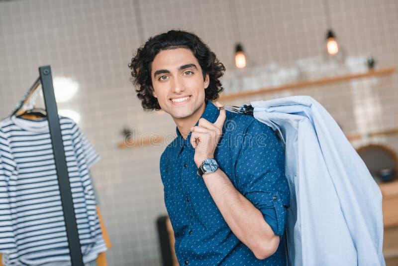 拿着与时髦的衬衣的挂衣架和微笑对在精品店的照相机的年轻人 库存照片