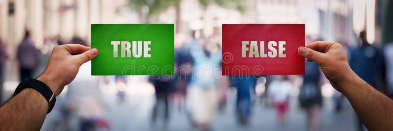 拿着与是的人手两不同彩纸板料和没有答复 正确挑选概念,做出正确的决定 免版税库存照片