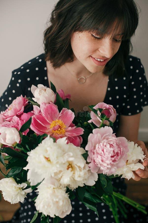 拿着与桃红色和白色牡丹的葡萄酒礼服的美丽的深色的女孩现代花束 有牡丹的愉快的时髦的妇女 免版税图库摄影
