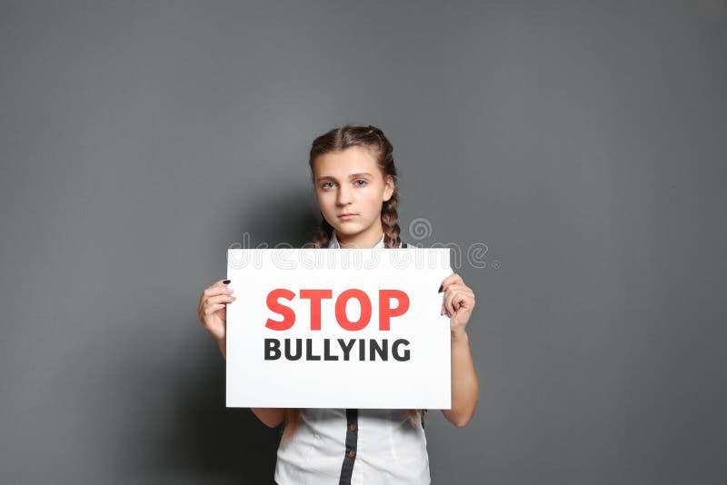 拿着与横渡的词的十几岁的女孩标志 免版税库存照片