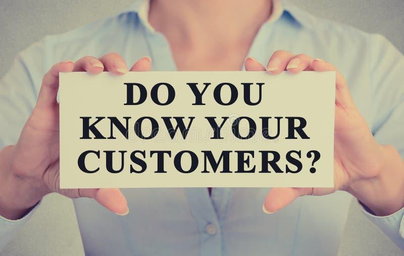 拿着与消息的女实业家手标志您认识您的顾客 免版税库存照片