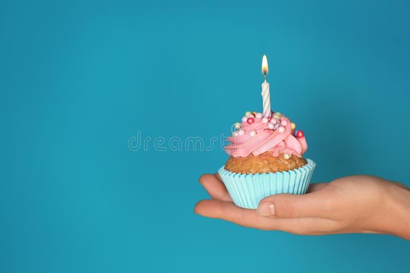 拿着与燃烧的蜡烛的女性手可口生日杯形蛋糕在颜色背景 免版税库存图片