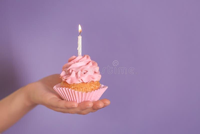 拿着与燃烧的蜡烛的女性手可口生日杯形蛋糕在颜色背景 免版税库存照片