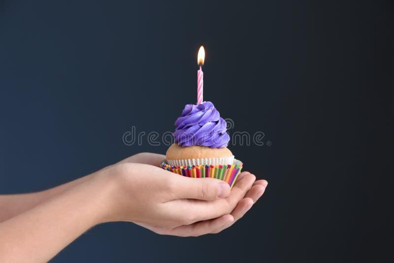 拿着与燃烧的蜡烛的女性手可口生日杯形蛋糕在黑暗的背景 免版税库存图片