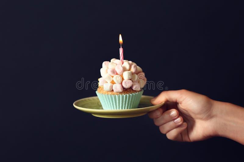 拿着与燃烧的蜡烛的女性手可口生日杯形蛋糕在黑暗的背景 免版税图库摄影