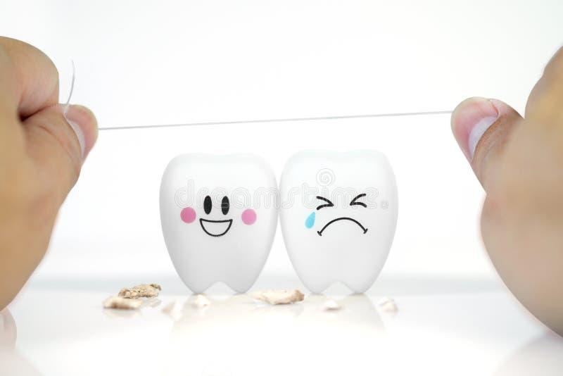 拿着与牙的人的手牙线微笑和哭泣情感 免版税库存照片