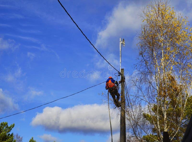 拿着与电工的电机工程师安全帽工作在与桶水力举的电力杆 库存图片