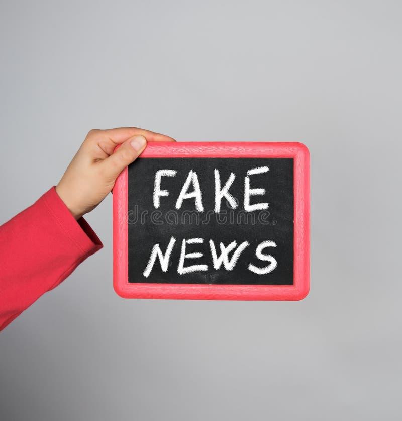 拿着与白垩题字假新闻的女性手红色框架 库存图片