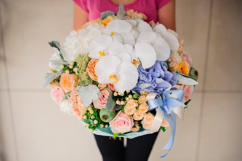 拿着与白色兰花的女孩美丽的混合花花束 免版税库存照片