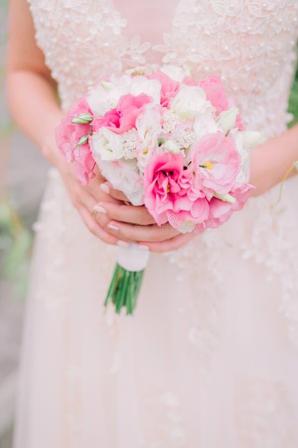 拿着与白色和桃红色花的新娘婚姻的花束在她的手上 免版税库存照片