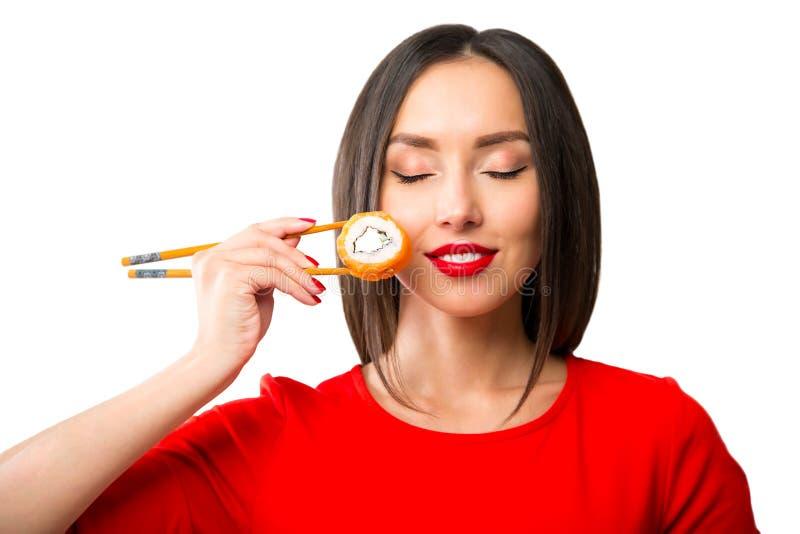 拿着与的少妇寿司筷子,隔绝在白色 免版税库存照片