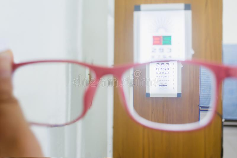拿着与眼睛测试图的手玻璃 库存图片