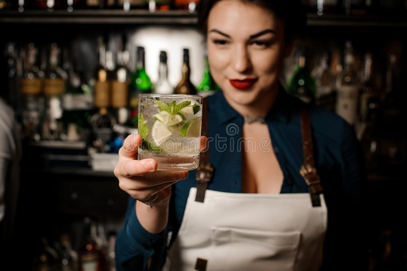 拿着与石灰和薄菏的侍酒者女孩一个新鲜的鸡尾酒 图库摄影