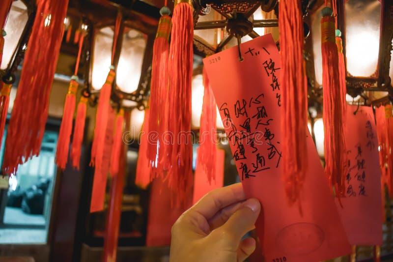 拿着与祷告的手一张卡片垂悬从在东华三院文武庙的一个灯笼在香港 免版税库存图片