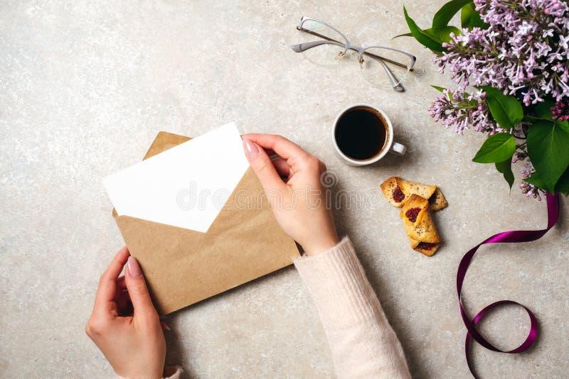 拿着与空插件的妇女手牛皮纸信封在用咖啡杯装饰的女性书桌,曲奇饼,淡紫色花和 免版税库存图片