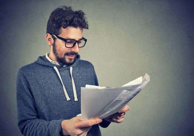 拿着与结果的愉快的人读书纸 库存照片