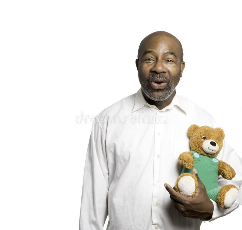 拿着与绿色套头衫的非裔美国人的人可爱的画象一个玩具熊隔绝在白色背景 免版税库存图片