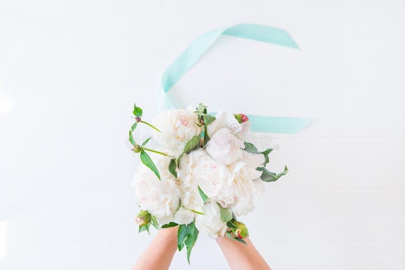 拿着与缎丝带的顶视图女性手美丽的白色牡丹花束在轻的背景 新娘概念礼服婚姻纵向的台阶 新娘花 免版税库存照片