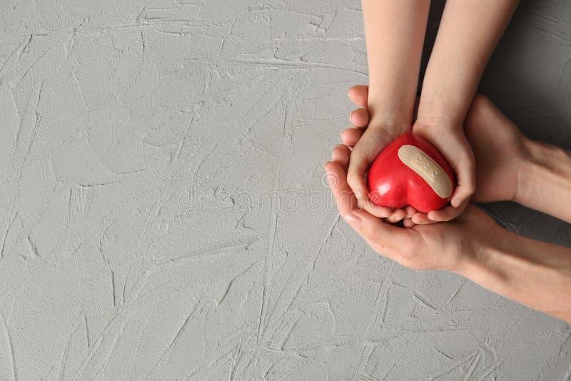 拿着与膏药的母亲和孩子的手红心在轻的背景 r 免版税库存图片
