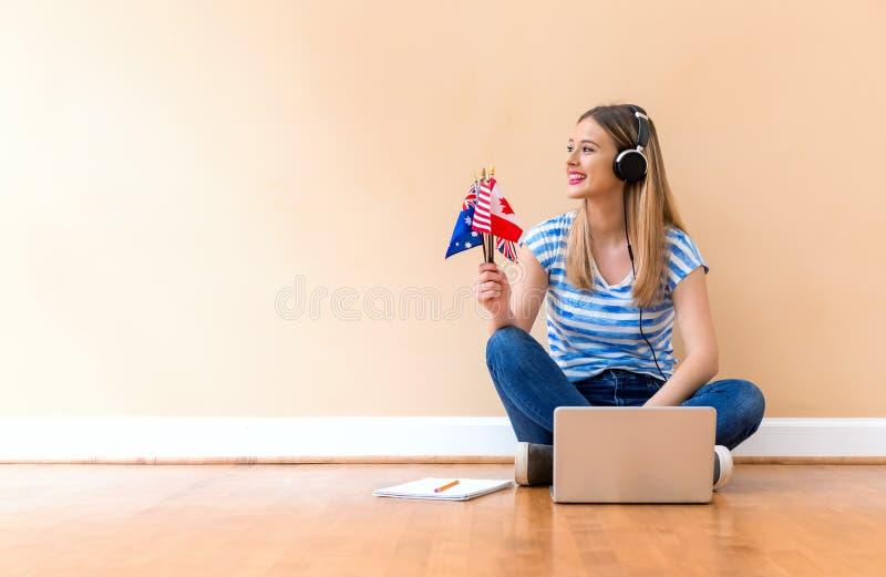 拿着与膝上型计算机的年轻女人英文国旗 免版税库存图片