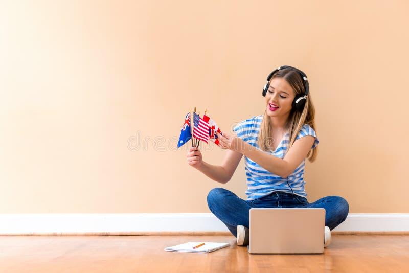 拿着与膝上型计算机的年轻女人英文国旗 免版税库存照片